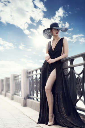 Fashion Woman in Hat and Black Dress Outdoor. Elegant Lady in Summer Hat long Evening Gown in City Promenade. Luxury Fashion Model on bright Sunny Sky Background next Fence. Riga City Quay Foto de archivo