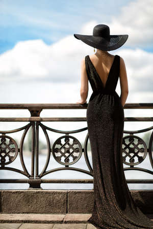 Woman Back Side View in Hat and Evening Dress Outdoor. Fashion Model Rear View looking away. Luxury Lady in long Gown at Promenade looking at Sky Foto de archivo