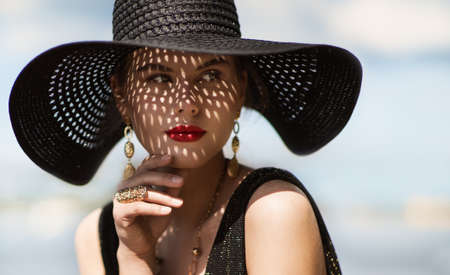 Woman in Hat Portrait. Fashion Luxury Model in Black Summer Hat with Make up and Golden Jewelry. Close up Beauty Face over Sky Background