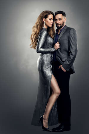 Fashion Woman Man Couple. Luxury Model Girl in Silver Dress holding Man elegant Suit. Provocative Stylish Romantic Pair over Gray Studio Background Foto de archivo