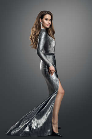 Fashion Model in luxury Silver long Dress. Elegant Woman with Curly Long Hair Hairstyle in Evening Gown with Slit showing Leg over dark Gray Studio Background Stockfoto