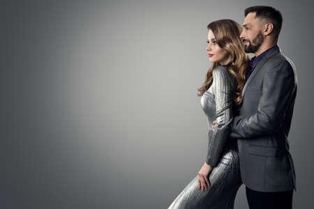 Fashion Stylish Man Woman Profile Side View. Bearded Man in Suit holding Luxury Model. Elegant lady in Silver Dress with Boyfriend over Gray studio Background Foto de archivo