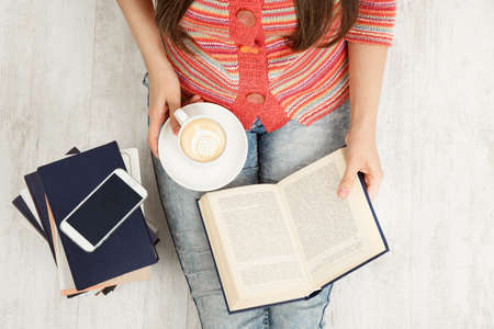 Close up Women Hands Holding Coffee Cup and Reading opened Book. Top view of Woman with Teacup having Break. Sitting Young Girl Study Books