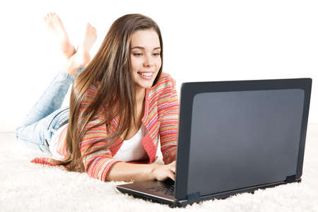Happy Woman working on Laptop. Young Girl typing on Computer Keyboard. Woman looking at Screen and write over White Background Foto de archivo