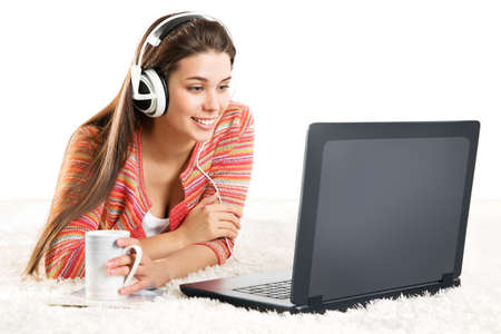 Smiling Woman use Laptop in Headphone. Young Girl work on Computer at Home. Happy Student Study in Earphone lying down and looking at Notebook Screen over White Background Foto de archivo