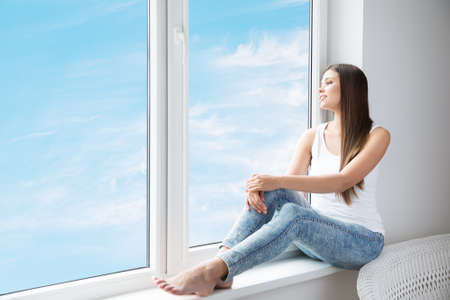 Woman looking at Window dreaming relaxing at Home. Attractive Girl on Window Sill thinking look forward on Bright Sunshine Sky. Lonely Woman at Home