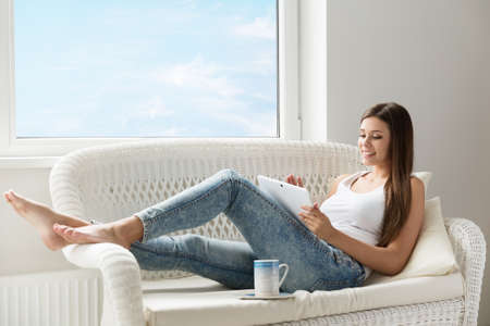Woman reading Tablet at Home lying down at Sofa next Window. Morning Coffee Break. Beautiful Happy Girl resting with Digital Touch Pad in White Room