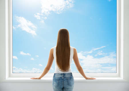 Woman Rear View looking at Window. Young Girl Back Side Silhouette look forward and thinking. Morning wake up Woman. Sky Background Foto de archivo