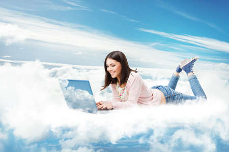 Woman using Laptop on Cloud. Happy Young Girl typing on Computer Lying Down. Cloud Technology Internet Information Data Concept. Online E Learning Study Foto de archivo