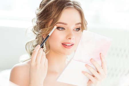 Bride Wedding Makeup. Bridal Make up. Beautiful Woman looking at Hand Mirror and putting Eye Shadow Eyebrow Self Make up in White Room