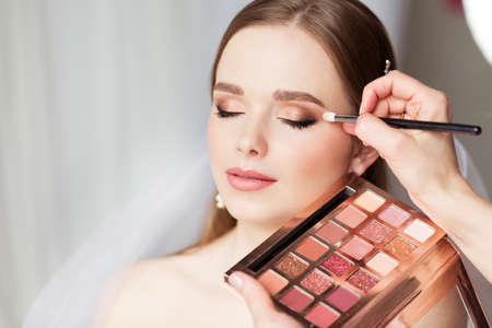 Wedding Make up Artist making Professional Bride Makeup. Bridal Eyeshadow Palette. Wedding Cosmetics Salon Face. Close up Beauty Bride Face Closed Eyes