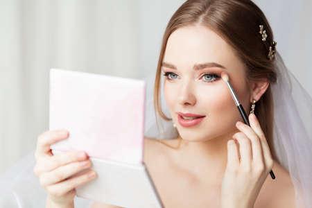 Bride Make up. Bridal Wedding Makeup. Eyeshadow Make up Application. Beauty Model holding Brush applying Eye Shadow looking at Mirror. Self Make up Foto de archivo