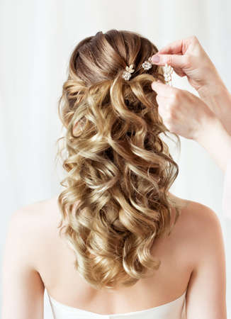 Wedding Hair Style Back Side View. Bride Hairstyle Accessory Rear View Close up. Hairdresser putting Flower Crystal Hairpin. Wavy curl Evening Hairdo over White Background Foto de archivo