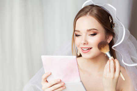 Bride Face Make up Finish. Bridal Wedding Makeup Close up. Skin Foundation Application. Happy Beauty Model holding Blush Brush looking at Mirror. Perfect Smooth Skin Color Texture