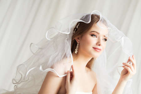 Bride in Veil. Wedding Make up and Bridal Hairstyle Fashion Portrait. Romantic Bride Looking Away at Window and Dreaming. Beauty Wedding Woman Face Close up over White Foto de archivo
