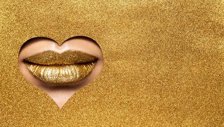 Golden Lips Make up. Gold Beauty Woman Makeup Face. Gold Lipstick Close up peek out Glitter Yellow Paper Background. Luxury Make up Cosmetic Salon Treatment