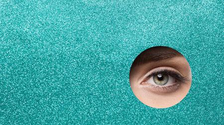 Eye Close up. Beauty Woman Eye Macro Make up. Green Pupil Eye Makeup Closeup looking out Hole Glitter Blue Paper. Eyelashes Extensions, Eyeliner, Eye Correction