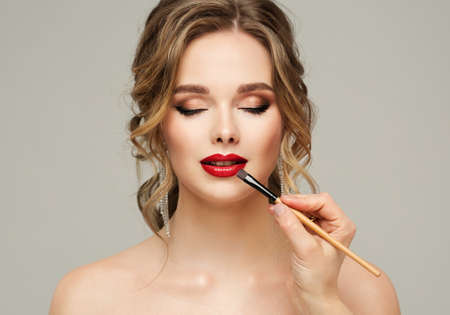 Make up Artist apply Red Lipstick. Beauty Woman Model put on Lip Gloss. Close up Portrait of Professional Makeup Master Hand with Lip Brush. Gray Background Banque d'images