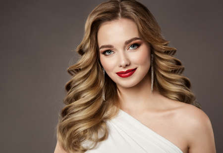 Hair Beauty Woman Portrait. Model Girl Luxury Hairstyle and Red Lips Make up. Volume Curly Blonde Hair Style. Elegant smiling Lady over Gray Studio Background Foto de archivo