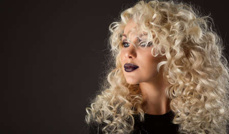 Curly Hair Beauty Woman. Blonde Model with Wavy Hairstyle Curls. Fashion Make up Face. Glamour Girl Portrait over Black Studio Portrait Foto de archivo