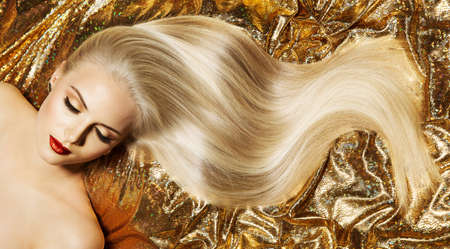 Beauty Blonde Hairstyle Model. Shiny Straight Long Golden Blond Hair Close up. Glamour Luxury Woman Perfect Skin Face Make up. Fashion Woman lying down over Gold Fabric