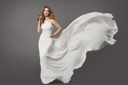 Woman in White Dress. Beauty Bride Model in Wedding Gown Flying on Wind over Gray Background. Bridal Fashion Clothing, Curly Hairstyle and Make up