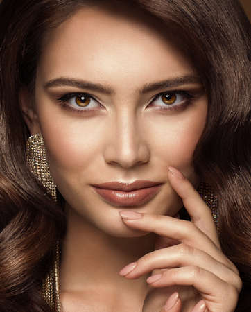 Beauty Woman Face Make up. Fashion Model Close up Portrait. Lips and Smokey Eyes Makeup. Beautiful Brunette with Gloss Lipstick looking at Camera