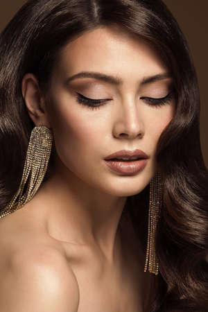 Beauty Woman Eyes Closed Makeup Portrait. Luxury Fashion Girl with Jewelry Earring. Woman Face Eye Shadow Cosmetic Make up and Shining Brown Hair Closeup Foto de archivo