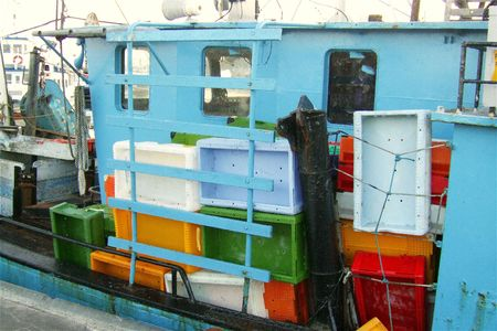 fishingboats: blue fishing boat with coloured crates Stock Photo