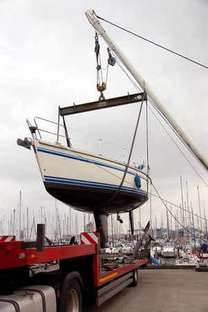 Sailing yacht lifting for transport at a truck