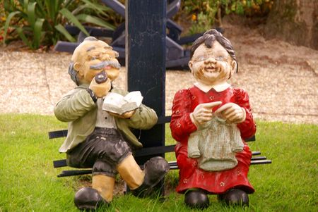 A pensionable couple as a garden statue Stock Photo