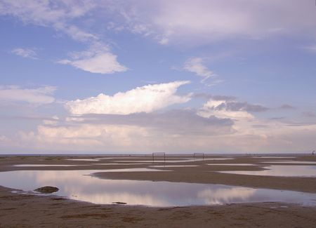 The beach at low tide with reflections of the clouds in the water Stock Photo - 3480209