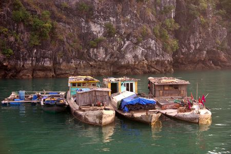 Fishing vessels at the floating village in Halong bay in Vietnam photo