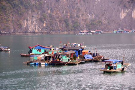 Fishing boats at the floating village in Halong bay in Vietnam photo