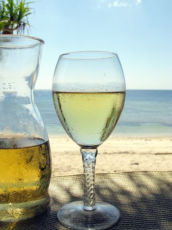 A carafe and a glass white wine at the beach Фото со стока