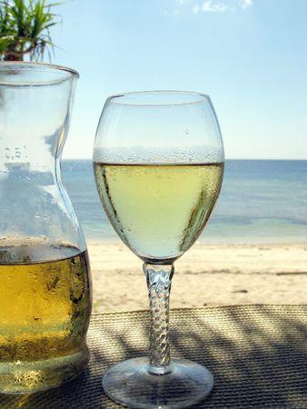 A carafe i szkła białego wina na plaży