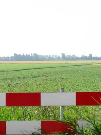 flakkee: A red and white gate with agricultural fields