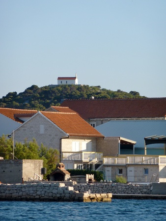 Houses in Betina with the church of Murter at the hill in Croatia photo
