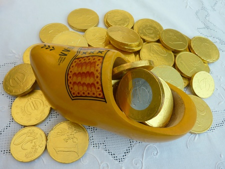 characterizing: A yellow chidren wooden shoe with euro coins from Sinterklaas Stock Photo