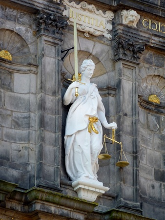 A statue of lady justice with the sword and the balance scales Фото со стока