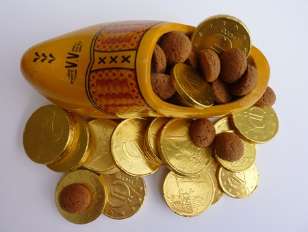 characterizing: A yellow wooden shoe with euro coins and spicy nuts