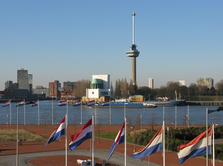 Skyscrapers and the Euromast along the river Meuse in Rotterdam in the Netherlands with the Dutch national flags Stock Photo