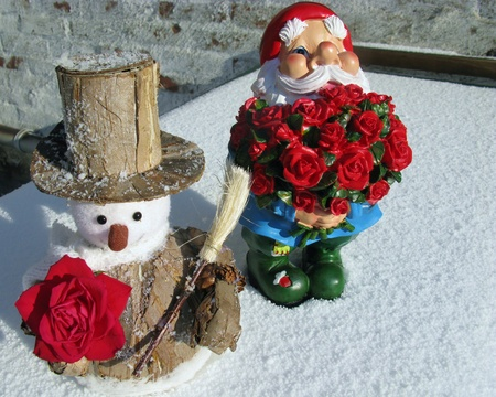 kobold: A garden gnome with a bunch red roses and a snowman with one rose in the snow for Valentines day