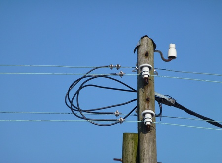 plassen: Above ground electricity wires and a wooden mast with insulations of porcelain Stock Photo