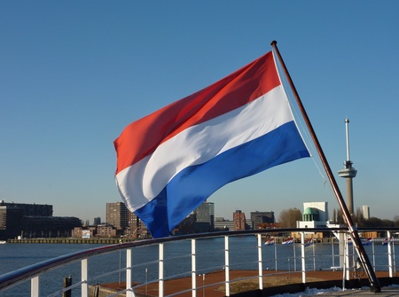 euromast: The dutch flag at the back of a ship anchored in the river Meuse in Rotterdam Stock Photo