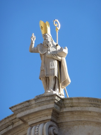 The statue of Saint Peter at the top of the St Blaise church in historic Dubrovnik in Croatia photo