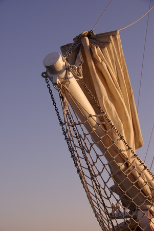 A bowsprit with a sail as a silhouette against a blue sky photo