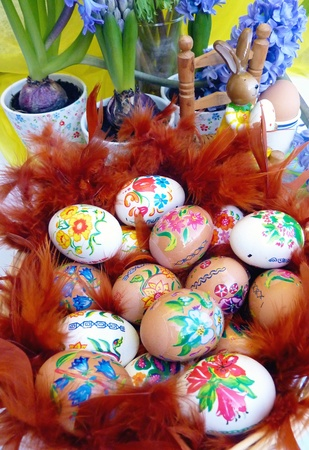 Colorful easter eggs in a basket with feathers photo