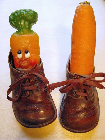 Children shoes with a fresh carrot and a carrot of narzipan