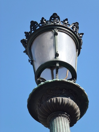 An antique lamppost in a city photo